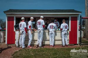 Baseball players line up at concession stand for hot dogs.