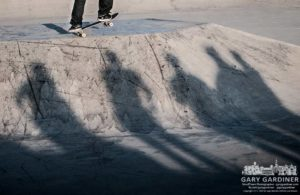Skateboarder's friends watch during afternoon at park