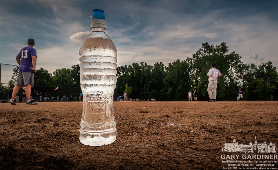 A chilled bottle of water for the first base coach sits at the edge of the field during the semi-finals of teh summer league at Huber village park.<br>My Final Photo for July 16, 2013.