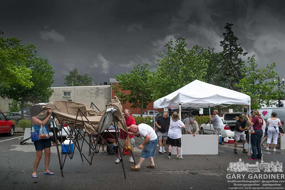 Customers and vendors struggle to dismantle their booths at the Uptown WestervilleFarmers Market as a heavy thunderstorm approaches. My Final Photo for July 10, 2013.