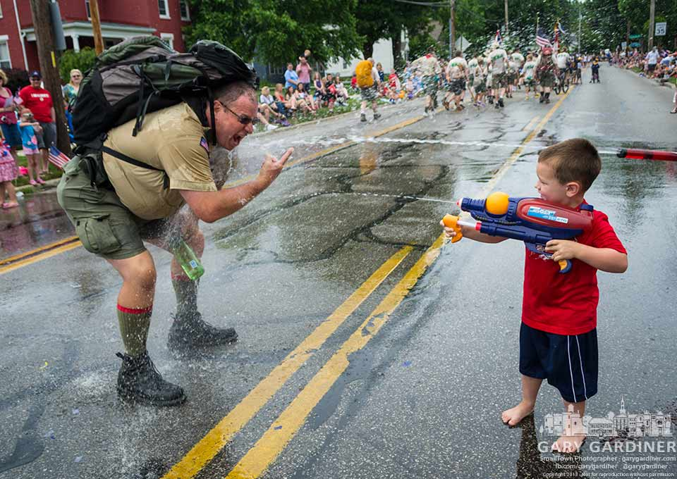 Boy Scout leader encourages a youngster with a water gun to quench his thirst and cool him down near the end of the 4th of July parade in Uptown Westerville.