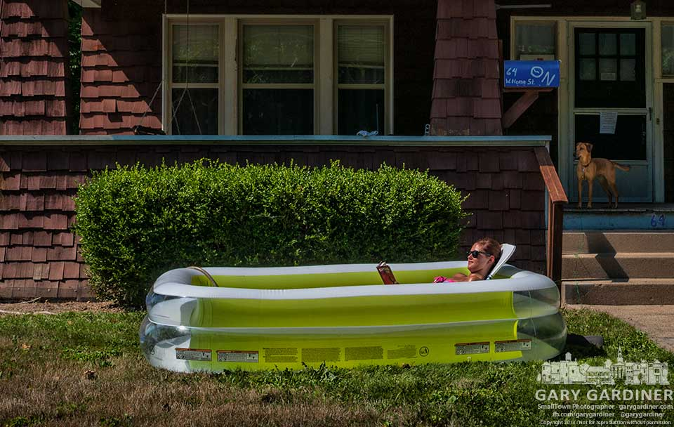 An Otterbein student takes a break from studies to read a novel in an inflated pool in front of the Theta Nu sorority house. My Final Photo for July 17, 2013.