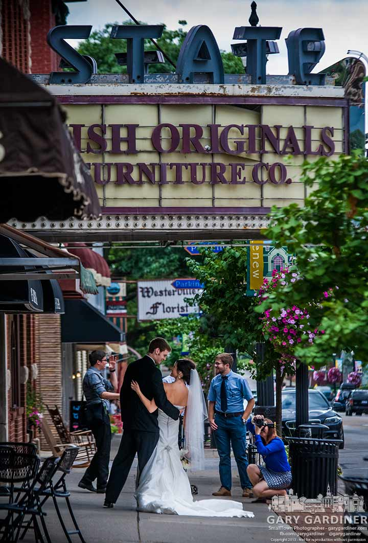 Photographer poses the happy couple beneath the State Theater marquee for the last of a series of wedding photos in Uptown.