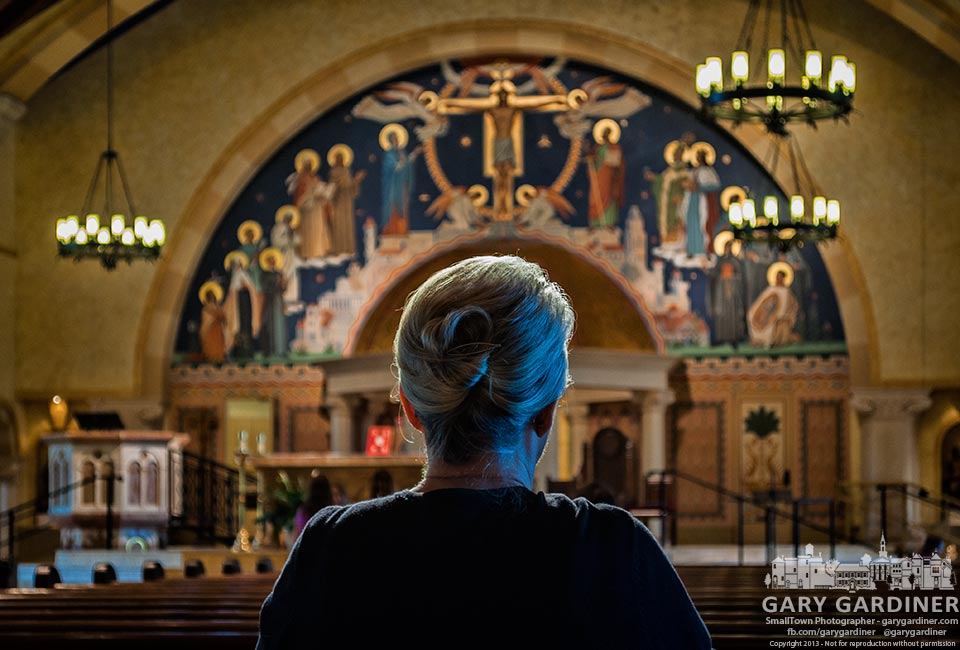 Light from the evening sun shining through overhead stained glass windows illuminates a parishioner at St. Paul Catholic Church. My Final Photo for Aug, 11, 2013.