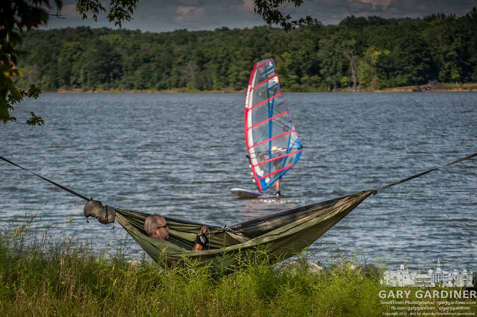A cyclist takes a break in his lightweight hammock stretched between two trees on the shore of Hoover Reservoir as a sailboarder runs in the wind. My Final Photo for Aug. 4, 2013.
