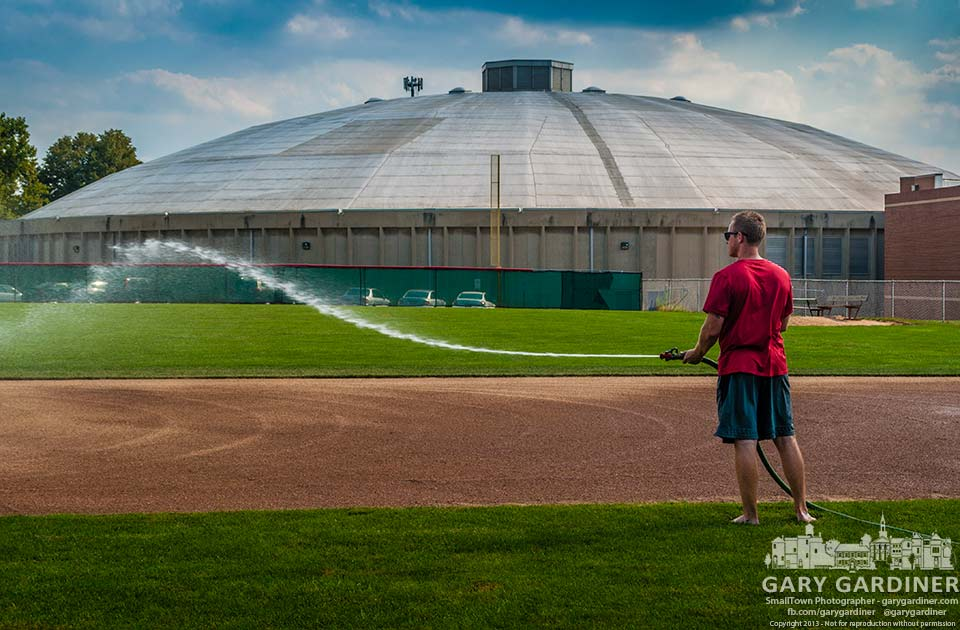 Otterbein graduate assistant baseball coach John LaCorte waters down the infield getting it ready for the first day of practice Wednesday when athletes arrive at school. Final Photo for Aug. 19, 2013.