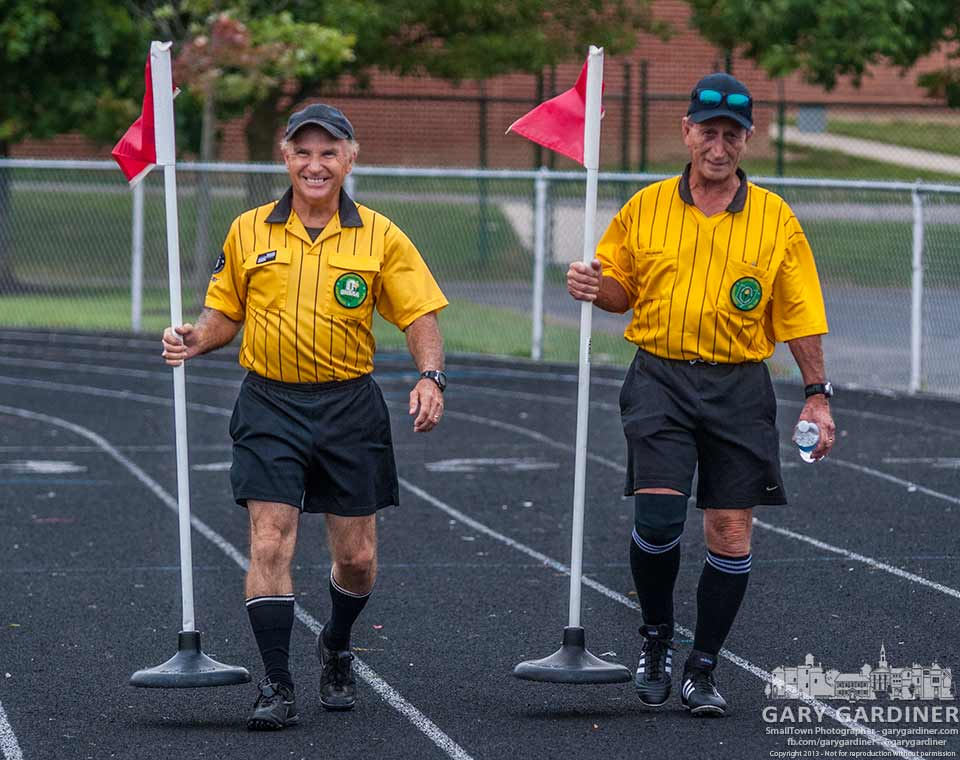 Referees for the Westerville South women's junior varsity soccer match carry markers to the field at halftime. My Final Photo for Aug. 22, 2013.