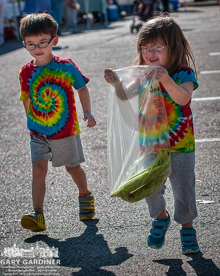 Twins wearing their matching tie-die shirts hustle corn home from the Uptown Westerville Farmers Market. My Final Photo for Sept. 4, 2013.