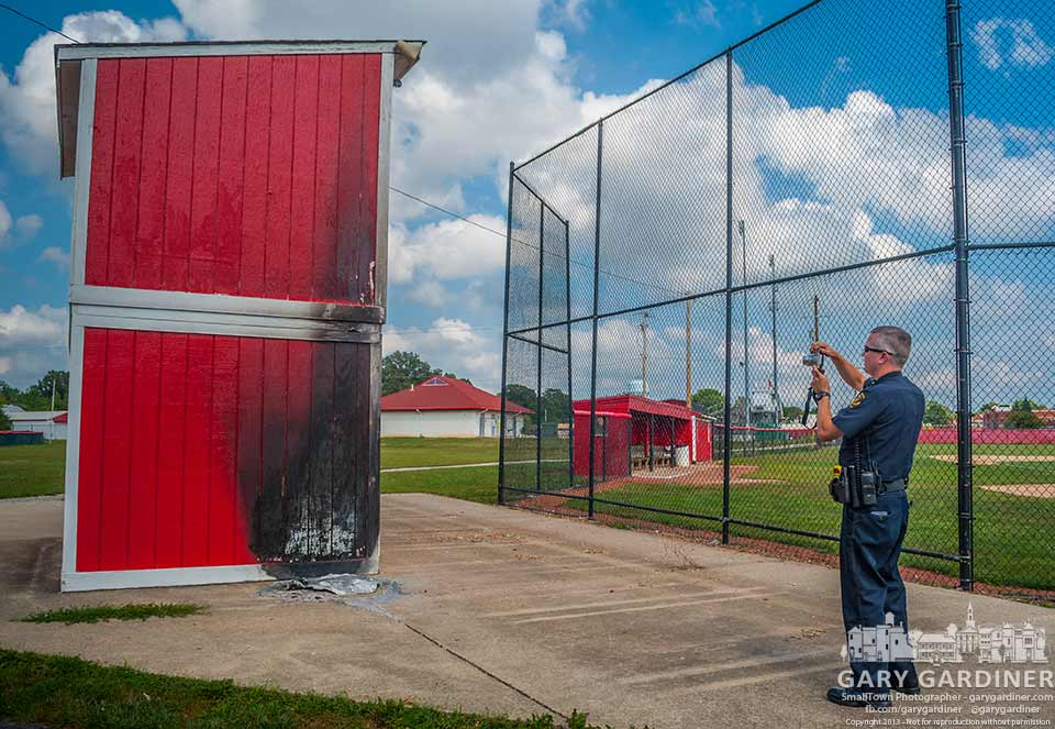 A Westerville police officer photographs damage to the pressbox at the Westerville South baseball field where a fire in a garbage can burned one side of the wooden structure. My Final Photo for Sept. 2, 2013.