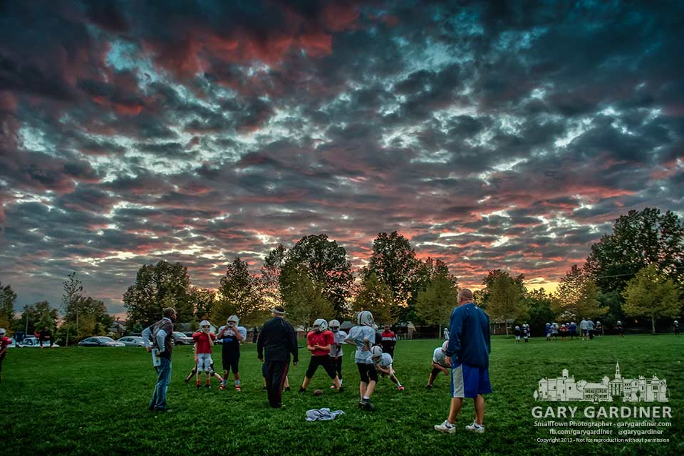 A youth football team practices under a pink and blue sunset sky on the fields of Huber Village Park. My Final Photo for Oct. 16, 2013.