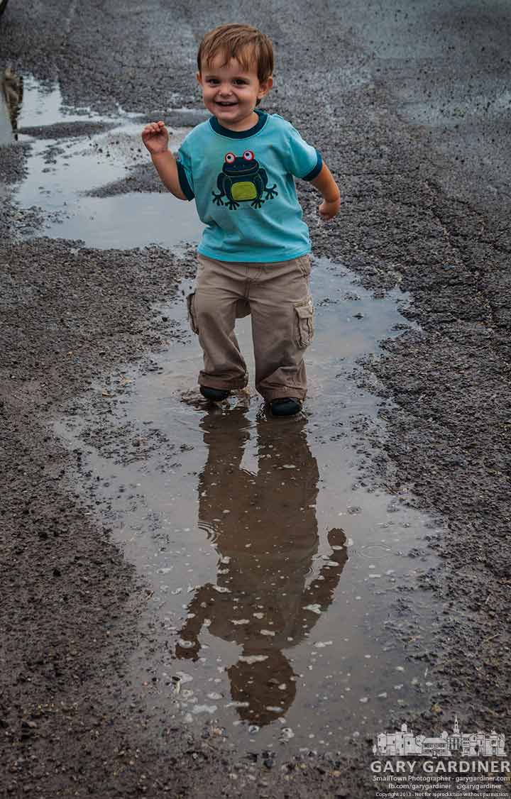 A youngster splashed through a puddle with his mother's permission as she shops at the Blendon Township Farmers Market. My Final Photo for Oct. 3, 2013.