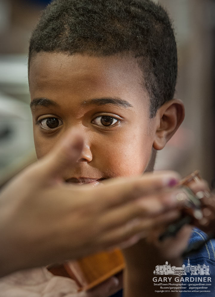 Twelve-year-old Mohamed Ali studies the hands of a sales person as he is introduced to the violin he will rent for his music lessons. My Final Photo for Oct. 11, 2013.