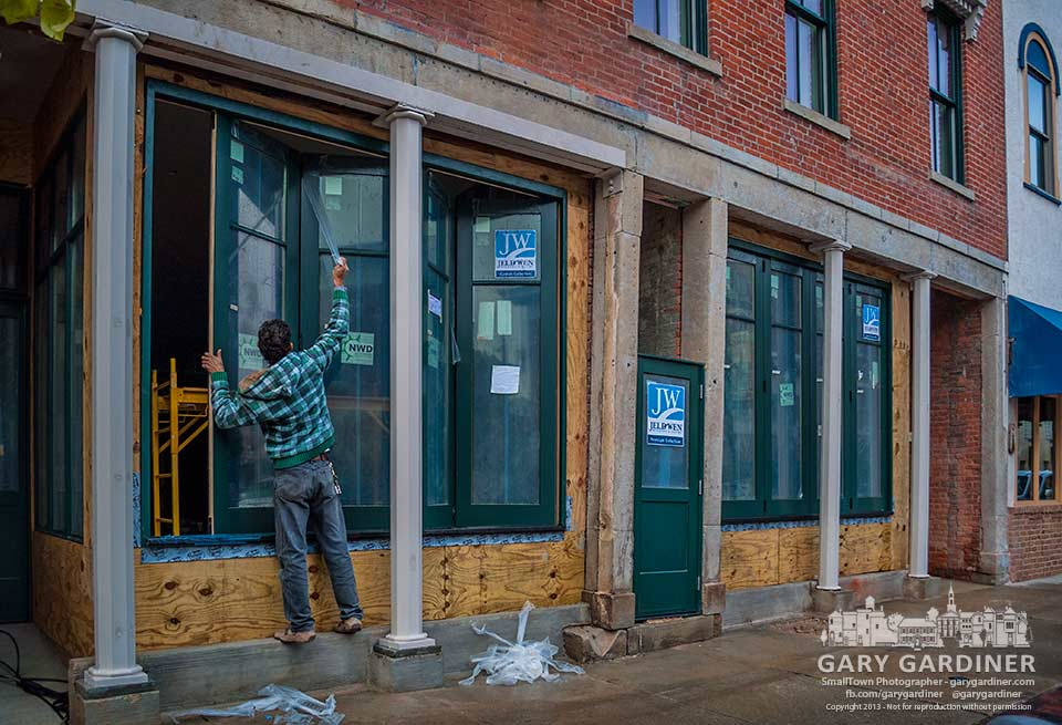 A worker removes a protective covering from newly installed windows in a renovated building in Uptown Westerville in preparation for a city inspection. My Final Photo for Nov. 5, 2013.