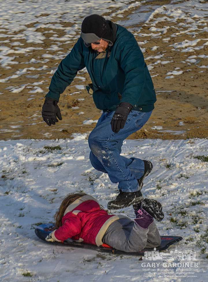 A father leaps over his daughter's sled as they play together on the small slopes along  the roadway at Alum Creek Park. My Final Photo for Dec. 7, 2013.