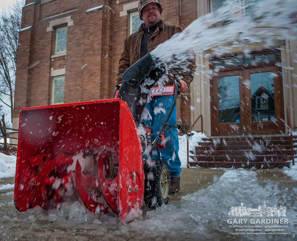 A worker removes snowy slush from the sidewalks at the First Presbyterian Church in preparation for Sunday morning services. My Final Photo for Dec. 14, 2013.