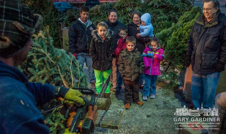 A family stands together watching as their choice of a Christmas tree is trimmed for their stand. My Final Photo for Dec. 13,. 2013.