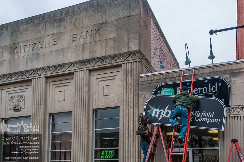Workers cover the Emerald Bank sign with a new sign declaring the bank's name change to Middlefield Banking Company. My Final Photo for Jan. 20, 2014.