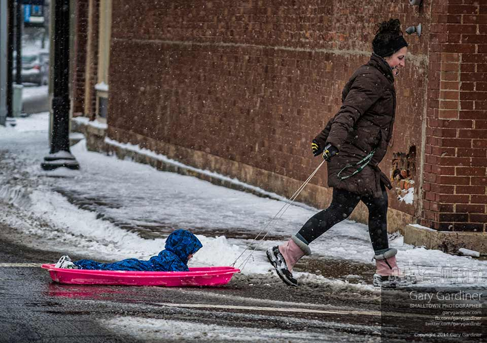A mom pulls her child along in a plastic sled across the snowy sidewalks and streets as they travel to the library in the middle of a record-setting cold day in Westerville. My Final Photo for Jan. 2, 2014