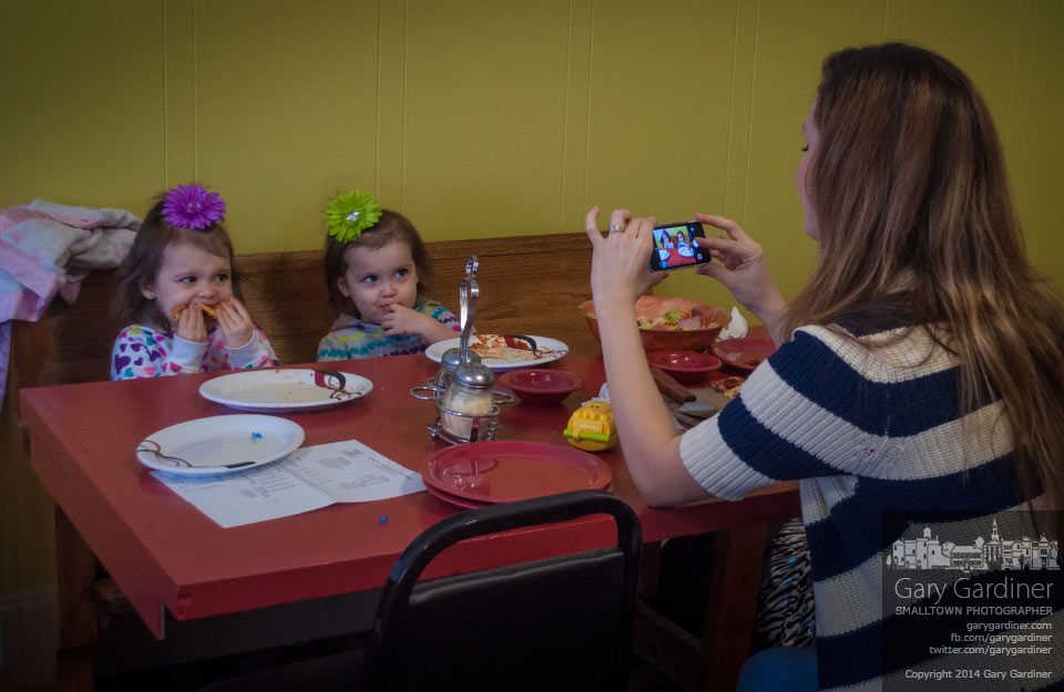 Kelly King photographs her twin daughters as they're eating pizza at Doughboy's Pizzeria in Uptown Westerville during the restaurant's soft opening for family and friends. My Final Photo for Jan. 18, 2014.