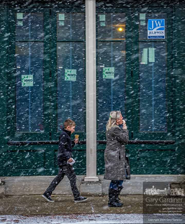 A mother and child enjoy ice cream cones as they walk through a snow squall in Uptown. My Final Photo for Jan. 17, 2014.