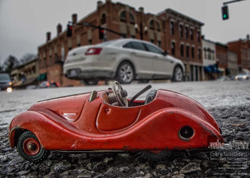 A red toy antique car sits in the intersection at State and College. My Final Photo for Jan 8, 2014.