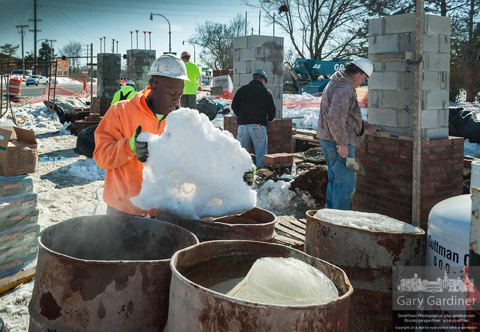 A bricklayer drops a block of frozen snow into a barrel to be melted into the water used to mix the mortar for the bricks being laid at the entrance to the city at State and Huber. My Final Photo for Feb. 18, 2014.