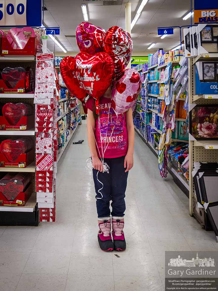 A young girl stands with the helium-filled heart-shaped Valentines balloons she bought on Valentines night for a day after party. My Final Photo for Feb. 14, 2014.