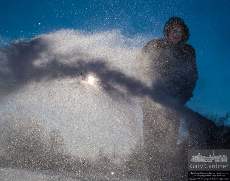 Twelve-year-old Cameron Voigt does a good deed by blowing snow from his grandparents sidewalks while they are away on a five day trip to Florida. My Final Photo for Feb. 7, 2014.