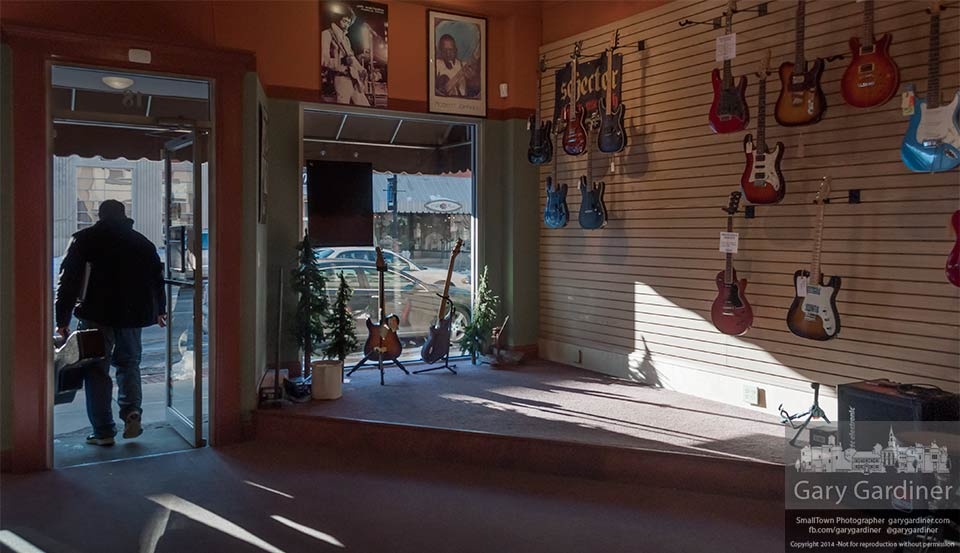 A music student steps through the door of Uptown Strings past the emptying walls of the guitar shop that will close leaving only the instructors at the store. My Final Photo for Feb. 13, 3014.