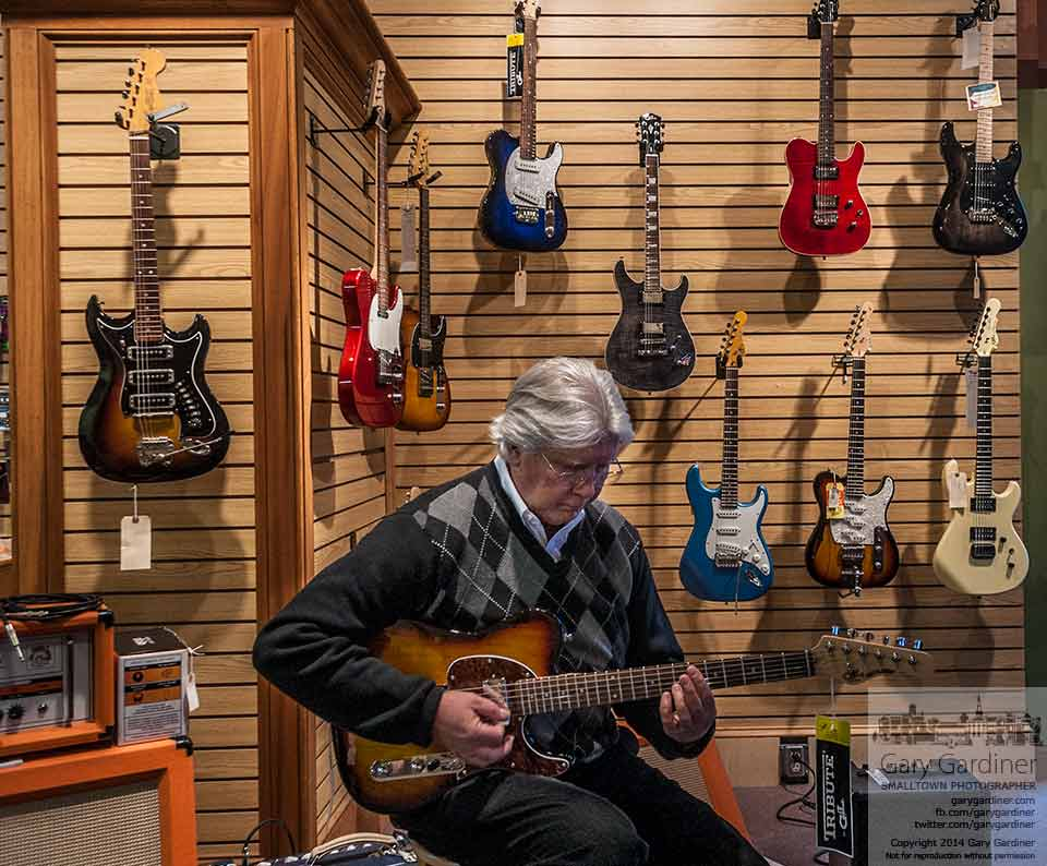 A musician quietly plays one of the remaining guitars at Uptown Strings during what will be the last week the retail portion of the store remains open. My Final Photo for Feb. 25, 2014.