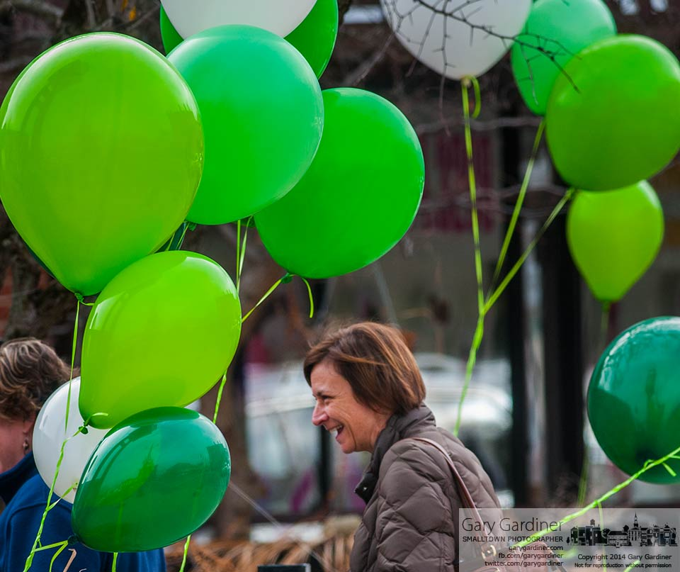 A woman navigates her way around and through wind tossed helium-filled balloons  attached to the gate posts at Jimmy V's patio entrance in celebration of St. Patrick's Day. My Final Photo for March 18, 2014.