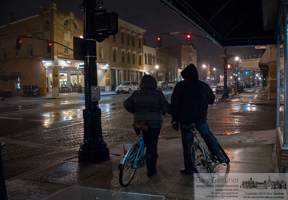 A couple riding bikes dutifully wait for the crossing signal at State and College during a nighttime ride at the beginning of what most people hope is the last snowfall of the season. My Final Photo for March 29, 2014.