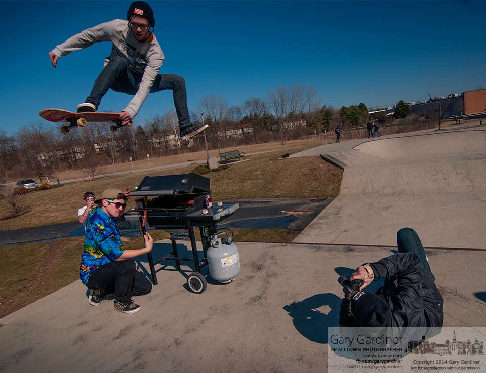 A skateboarder flies over the grill during a photo shoot at the Westerville Skate Park during the Spring Cookout marking the unofficial start of skate board season . My Final Photo for March 30, 2014.
