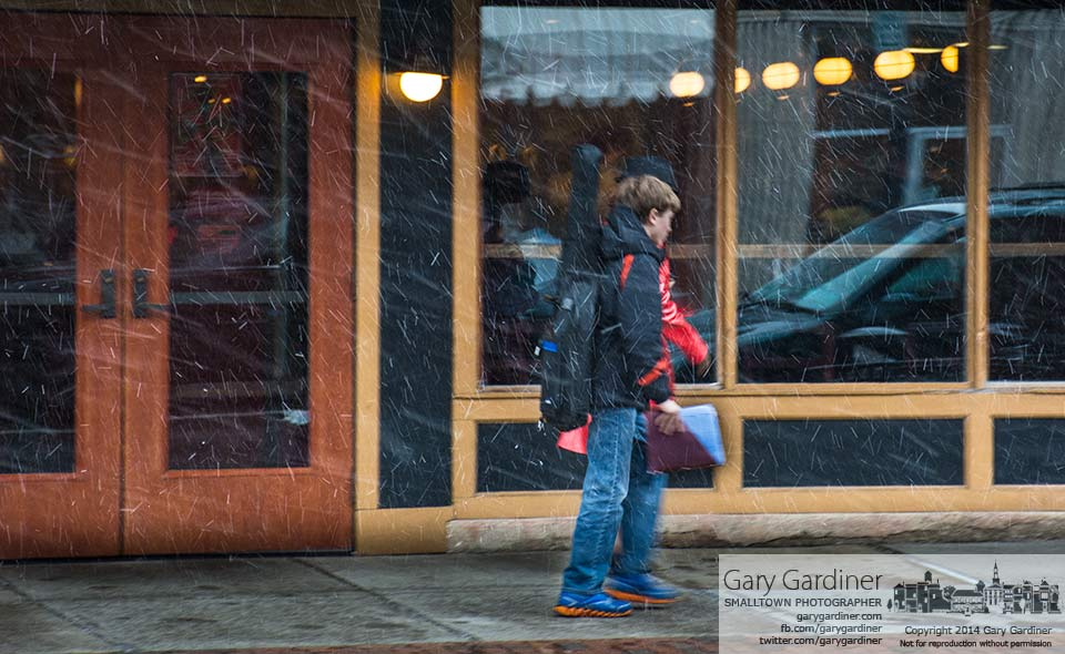 A young boy carrying his guitar and sheet music walk briskly through swirling snow with his mother as they traveled to Uptown Strings music classes. My Final Photo for March 12, 2014.