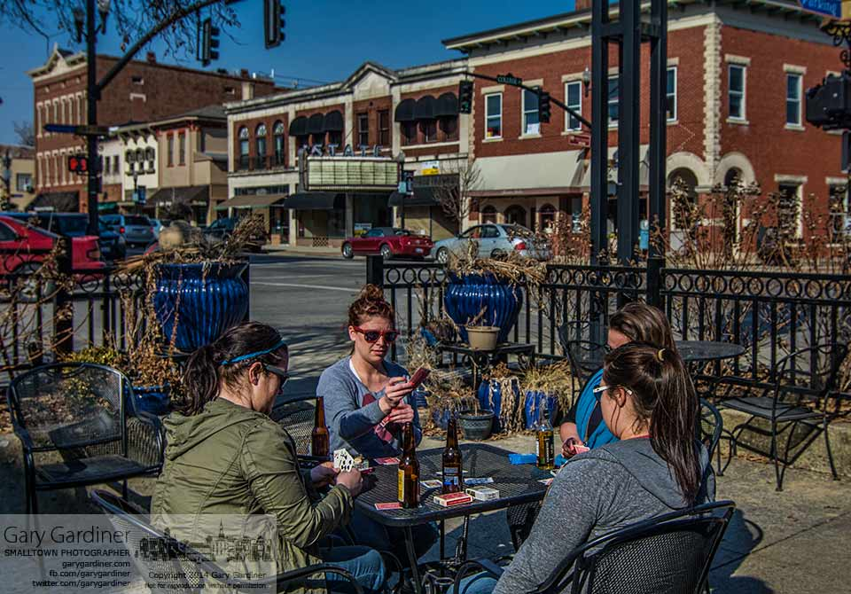 Four women enjoy liquid refreshment and  a game of cards in the warm sun on the patio at Jimmy V's in Uptown. My Final Photo for March 10, 2014.