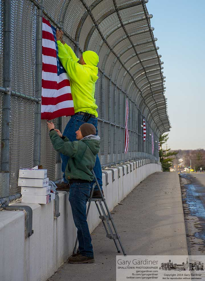 Blendon Township workers replace American flags on the Dempsey road bridge over I-270 earlier than expected after the severe winter damaged the flags beyond repair. My Final Photo for April 1, 2014.