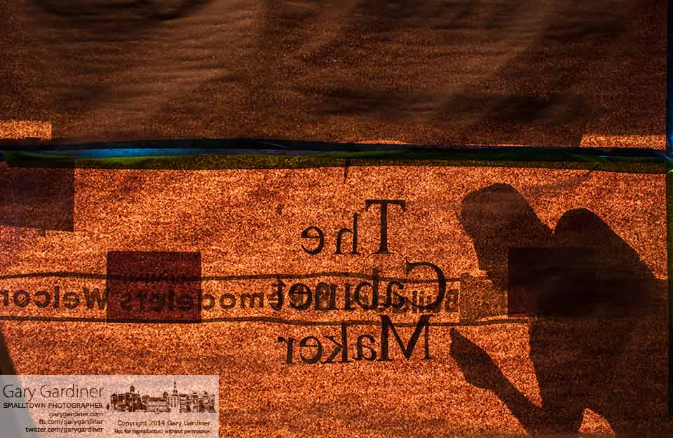 A sign maker's shadow falls across paper covering the glass on The Cabinet Maker's front windows as he applies the company's new logo. My Final Photo for April 0, 2014.