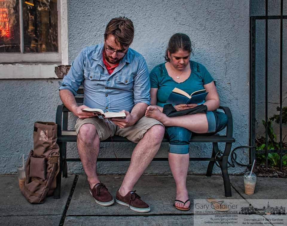 "Dan Middleton reads a John Dos Passos novel while his companion Jeannette Shively reads ""Mary Poppins"" while sharing a bench on the sidewalk on South State Street. The pair found a quiet spot to read and enjoy coffee from Java Central. My Final Photo for April 11, 2014."