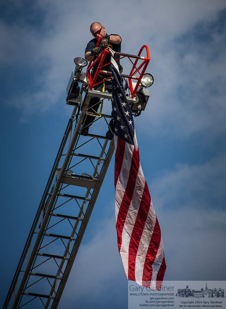 A Westerville fire fighter attaches a flag to the end of an extended fire truck ladder flying over State Street on the first Fourth Friday of the  summer season. My Final Photo for April 25, 2014.
