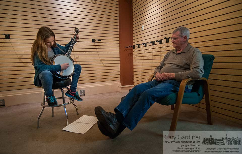 Eleven-year-old Joselin List practices before her banjo lessons at Uptown Strings while great-great-grandfather Ron Sherman watches and comments on her progress. My Final Photo for April 2, 2014.