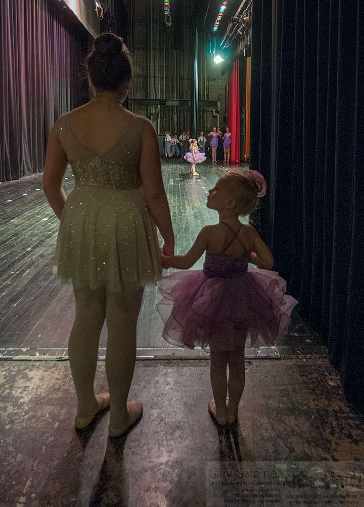 Under the tutelage of an older dancer a young ballerina waits for her cue to join other dancers on stage during recital rehearsals for Generations end of year performance. My Final Photo for May 2, 2014.