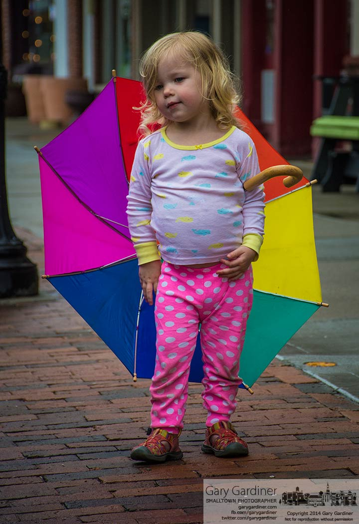 A young girl stands with her rainbow colored umbrella after a brief rain shower in Uptown Westerville. My Final Photo for April 30, 2014.