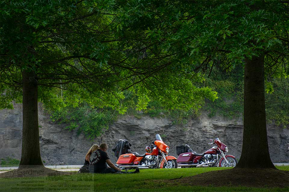 A motorcycling couple enjoys snacks under evergreen trees at a rest stop along the interstate highway in Kentucky. My Final Photo for May 28, 2014.