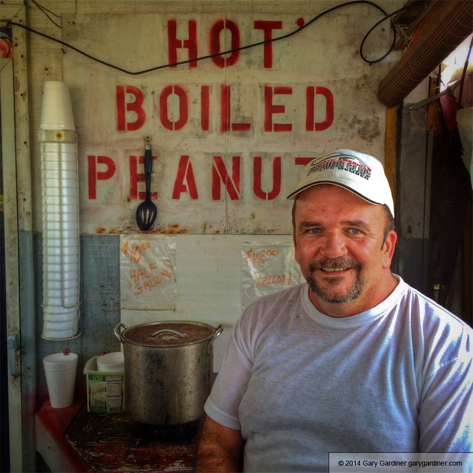 Tim poses for a photo in his BBQ/boiled peanuts/vegetables/peaches/Vidalia onions at Hogfather'z in Griffin, Ga. My Final Photo for May 25, 2014.