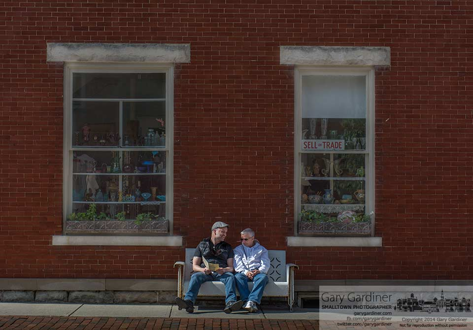 Two people enjoy each others company while sitting on a vintage metal porch swing sofa outside Westerville Antiques. My Final Photo for May 18, 2014.