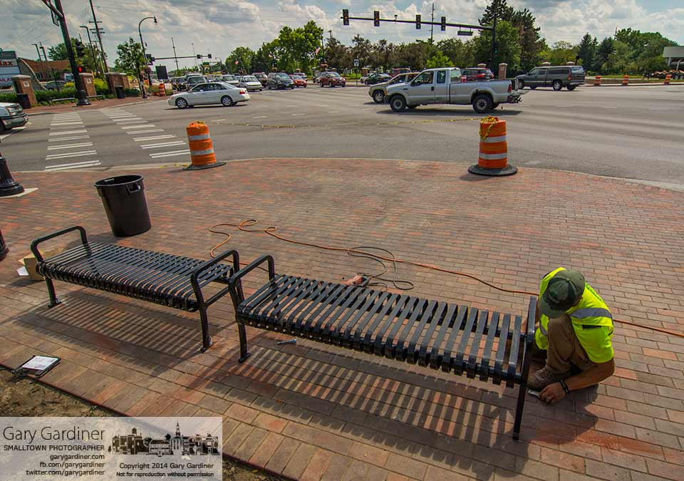 Workers install metal park benches at the four corners of State and Huber hoping to finish construction of the interchange in time for the July 4th parade. My Final Photo for June 26, 2014.
