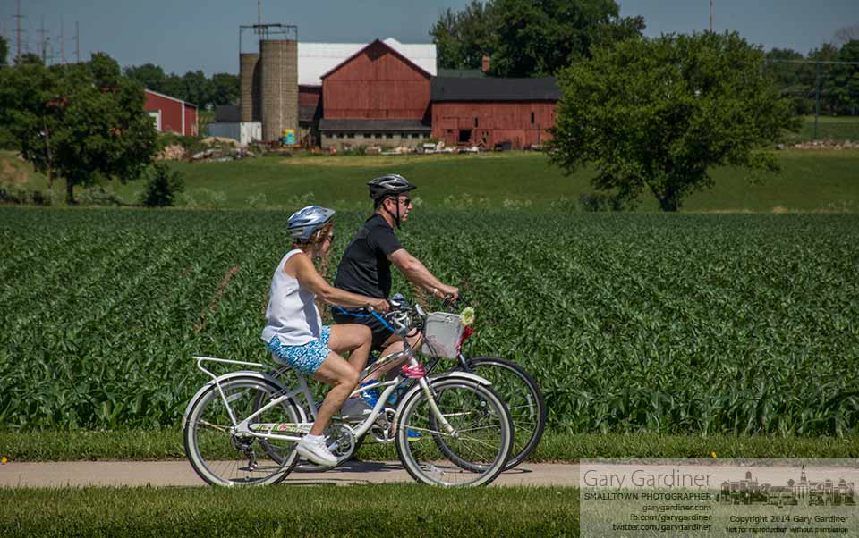 A pair of bicyclists ride along the sidewalk at the edge of the lower fields for the Yarnell Farm on Cleveland Ave. My Final Photo for June 14, 2014.