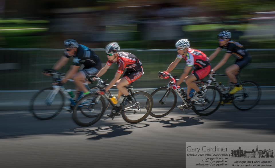 Racers run through shadows and light along Grove Street at Otterbein University in the first Westerville Bike Race. My Final Photo for May 31, 2014.