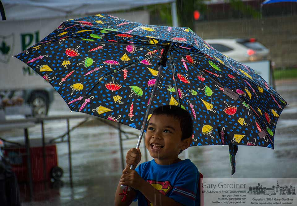 A young boy at the Uptown Westerville Farmers Market shields himself from an afternoon rain with an umbrella decorated with umbrellas. My Final Photo for June 4, 2014.