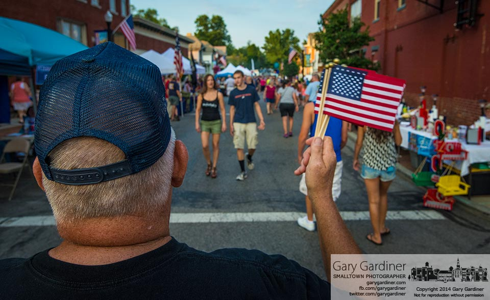 American Legion member Bob Nocks waves small flags  the group sells as a fundraiser during Fourth Friday's in uptown Westerville. My Final Photo for June 27, 2014.